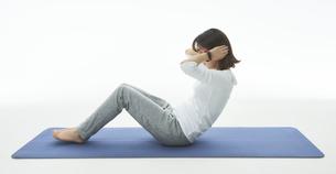 スマートウォッチをつけて腹筋をする女性の写真素材 [FYI04484199]