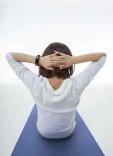 スマートウォッチをつけて腹筋をする女性の写真素材 [FYI04484200]