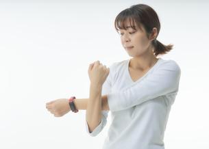 スマートウォッチをつけてストレッチをする女性の写真素材 [FYI04484203]