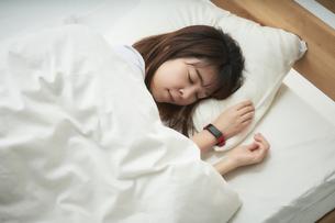スマートウォッチをつけて就寝する女性の写真素材 [FYI04484208]