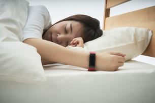 スマートウォッチをつけて就寝する女性の写真素材 [FYI04484210]