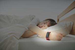 スマートウォッチをつけて就寝する女性の写真素材 [FYI04484212]