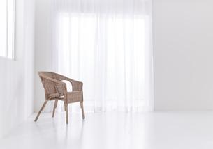 白い空間の中のラタンチェアーの写真素材 [FYI04484261]