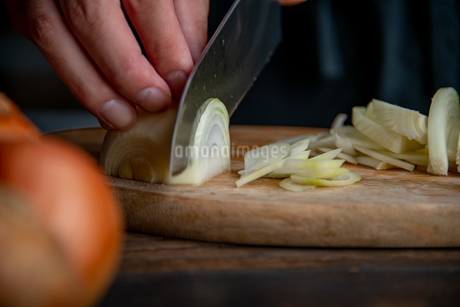 Slicing onion on cutting board in kitchen. Cooking image.の写真素材 [FYI04485353]