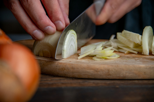 Slicing onion on cutting board in kitchen. Cooking image.の写真素材 [FYI04485354]