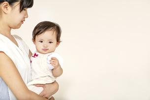 お母さんに抱かれカメラ目線の赤ちゃんの写真素材 [FYI04485996]