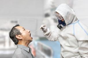 防護服を身に着け患者の喉から細菌を採取する医療従事者。の写真素材 [FYI04486393]