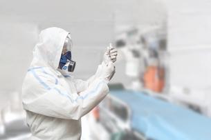 防護服を身に着け注射の準備をする医療従事者。の写真素材 [FYI04486394]