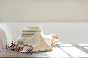室内にある木製のテーブルに置かれたタオルの写真素材 [FYI04487363]