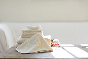 室内にある木製のテーブルに置かれたタオルの写真素材 [FYI04487364]