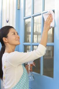 窓ガラスを磨く女性の写真素材 [FYI04487467]