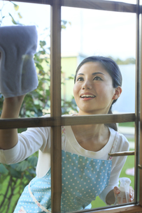 窓ガラスを磨く女性の写真素材 [FYI04487468]