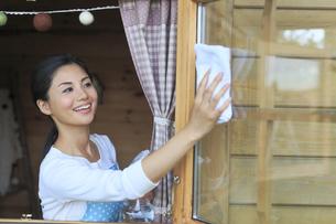 窓ガラスを磨く女性の写真素材 [FYI04487472]