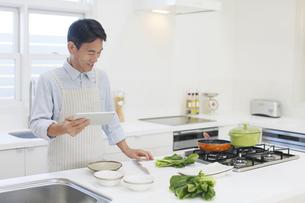 タブレットを見ながら朝食を作る中年男性 の写真素材 [FYI04487478]