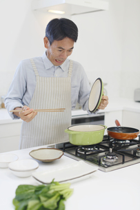 エプロンをして料理をする中年男性 の写真素材 [FYI04487505]