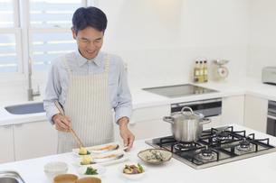 エプロンをして料理をする中年男性 の写真素材 [FYI04487506]
