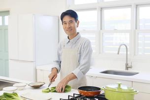 エプロンをして料理をする中年男性 の写真素材 [FYI04487512]