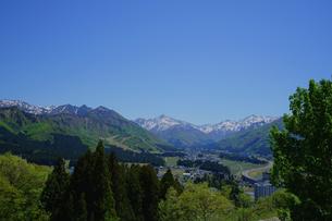 岩原高原から望む湯沢の街並みと高速のS字カーブ、新緑と冠雪の山が美しい春の風景の写真素材 [FYI04487794]