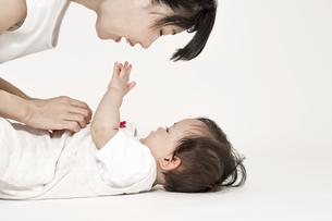 お母さんと見つめ合い遊ぶ女の子の赤ちゃん。育児,子育て,母性,愛情イメージの写真素材 [FYI04489189]