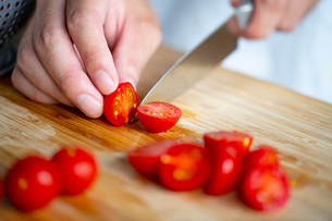 Man slicing cherry tomatoes on cutting board.の写真素材 [FYI04489197]