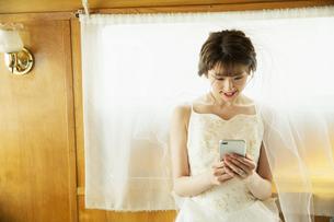 スマホを操作するドレス姿の20代女性の写真素材 [FYI04490353]