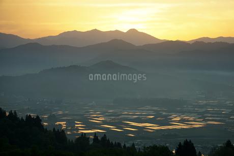 日本有数の米処南魚沼に広がる早朝の雲海と、太陽光を浴びて黄金色に光る田植え前の水田の写真素材 [FYI04492743]