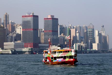 香港・ビクトリア湾を航行するスターフェリー。香港島と九龍半島の間で英国植民地時代から運行されている。これは観光船にも使われている仕様のものの写真素材 [FYI04493152]