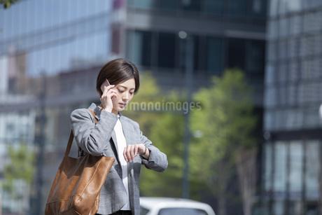 ビジネス街に佇むスーツを着た若いビジネスウーマンの写真素材 [FYI04493530]