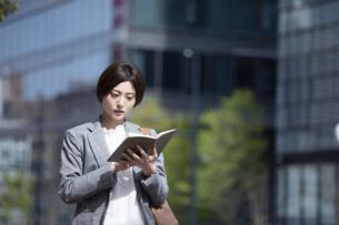ビジネス街に佇むスーツを着た若いビジネスウーマンの写真素材 [FYI04493535]