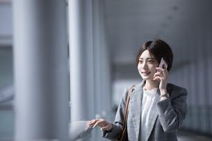ビジネス街に佇むスーツを着た若いビジネスウーマンの写真素材 [FYI04493538]