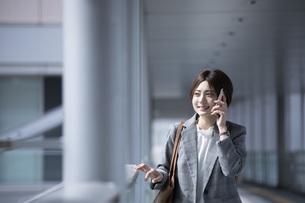 ビジネス街に佇むスーツを着た若いビジネスウーマンの写真素材 [FYI04493539]