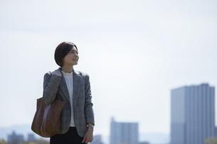 ビジネス街に佇むスーツを着た若いビジネスウーマンの写真素材 [FYI04493542]
