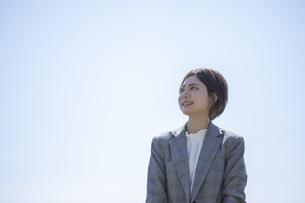 青空を背景に佇むスーツを着た若いビジネスウーマンの写真素材 [FYI04493545]