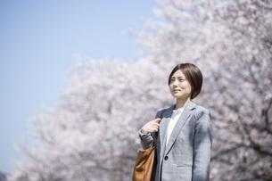 桜とスーツを着た若いビジネスウーマンの写真素材 [FYI04493551]