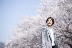 桜とスーツを着た若いビジネスウーマンの写真素材 [FYI04493552]