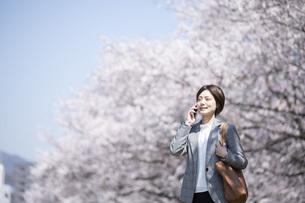 桜とスーツを着た若いビジネスウーマンの写真素材 [FYI04493555]
