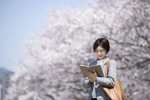 桜とスーツを着た若いビジネスウーマンの写真素材 [FYI04493557]