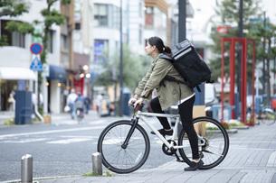 自転車で荷物の配送を行う若い女性の写真素材 [FYI04493625]