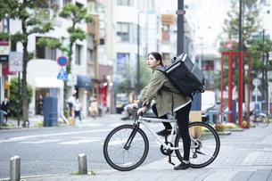 自転車で荷物の配送を行う若い女性の写真素材 [FYI04493626]