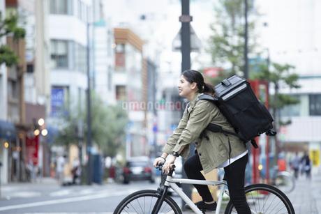 自転車で荷物の配送を行う若い女性の写真素材 [FYI04493627]