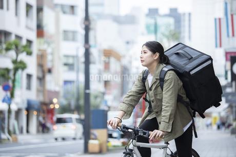 自転車で荷物の配送を行う若い女性の写真素材 [FYI04493629]
