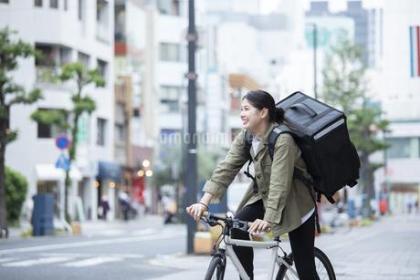 自転車で荷物の配送を行う若い女性の写真素材 [FYI04493631]