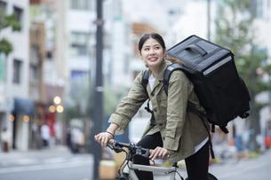 自転車で荷物の配送を行う若い女性の写真素材 [FYI04493632]
