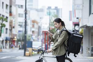 自転車で荷物の配送を行う若い女性の写真素材 [FYI04493633]