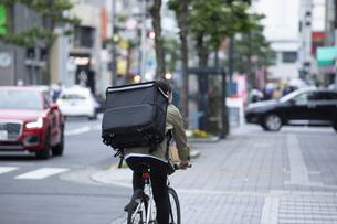自転車で荷物の配送を行う若い女性の写真素材 [FYI04493635]
