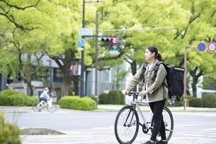 自転車で荷物の配送を行う若い女性の写真素材 [FYI04493638]