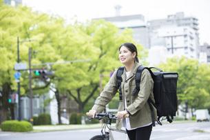 自転車で荷物の配送を行う若い女性の写真素材 [FYI04493639]