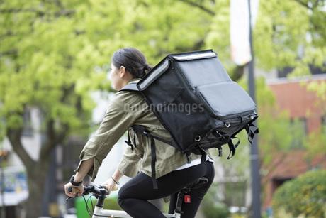 自転車で荷物の配送を行う若い女性の写真素材 [FYI04493640]