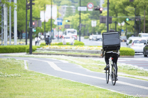 自転車で荷物の配送を行う若い女性の写真素材 [FYI04493641]