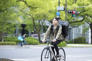 自転車で荷物の配送を行う若い女性の写真素材 [FYI04493642]